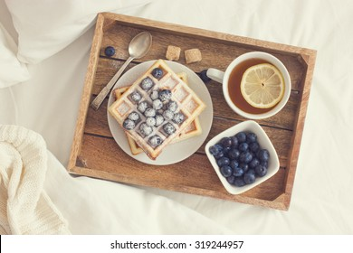 breakfast in bed,  tray with belgian waffles with blueberry and cup of lemon tea, toned, top view