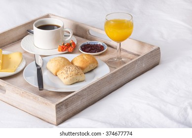 Breakfast in bed. A tray with coffee, bread, orange juice and cheese. Room service concept.