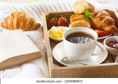 Breakfast in bed, tray of coffee, croissants, jam, strawberry and book. Honeymoon. Early sunny morning at the hotel. Selective focus