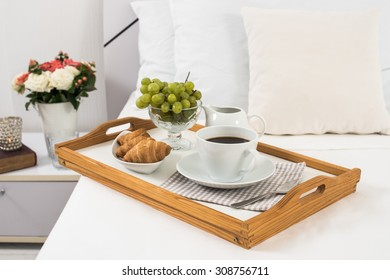 Breakfast in bed, tray with coffee, fruits and croissants on a bed with white linen in bedroom interior, hotel room