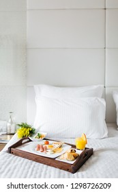 Breakfast in bed, a tray of juice, croissants, eggs, flowers. Honeymoon. Early morning at the hotel.