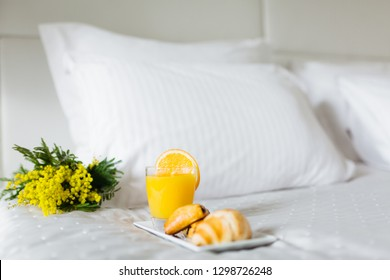 Breakfast in bed, a tray of juice and croissants,  Honeymoon. Early morning at the hotel.