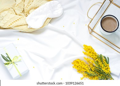 Breakfast in bed white flat lay frame composition with mimosa flowers, a cup of coffee and a gift. Concept woman's or mother's day top view. Copy space