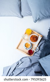 Breakfast Bed Wooden Tray Coffee Bun Grey Linens Bedding Sheet Pillow Coverlet Hotel Room Early Morning at Hotel Background Concept Interior Copy Space