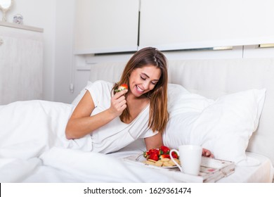 Breakfast in bed for young beautiful woman. Woman having breakfast in bed with fruits, coffee and biscuits. Morning waking up in hotel