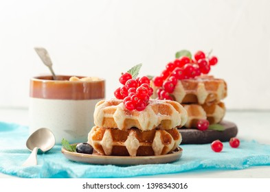 Breakfast with belgian waffles with honey caramel sauce and summer berries