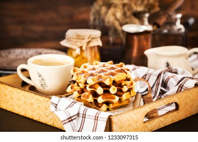 Breakfast with belgian waffles, jam and coffee on tray, rustic background