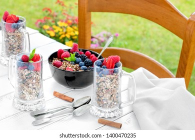 Breakfast with berries and cereals outside in the garden.