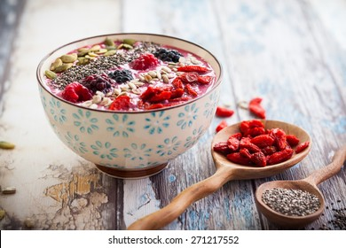Breakfast berry smoothie bowl topped with goji berries,raspberry, blackberry, pumpkin, sunflower and chia seeds. soft focus