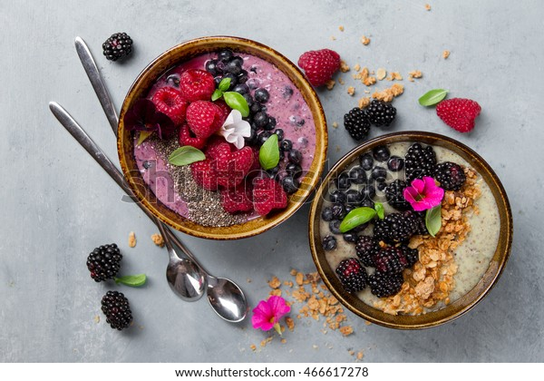 Breakfast berry smoothie bowl topped with blueberries, raspberry, blackberry, chia seeds, oat flakes and muesli for healthy breakfast, selective focus