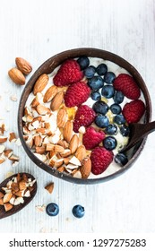 Breakfast berry smoothie coconut bowl topped with blueberry,almond, banana and raspberries on marble background. Top view. Close up.