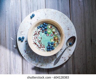 Breakfast blue spirulina coconut smoothie bowl topped with coconut flakes and berries on wood background, top view, toning.