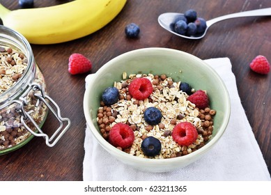 Breakfast bowl with fresh berry fruits. Cereals with blueberries and raspberries on a wooden table.