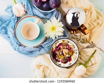 Breakfast with bowl of fresh quark, berries, seeds. Table setting with coffee and flowers