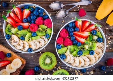 Breakfast bowl: granola with banana, kiwi, raspberry, strawberry, blueberry and chia seeds on wooden background