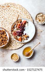 Frühstücksschüsseln mit Granola, Feigen, roten Weintrauben, Jogurt, Kokoschips und Honig. Gesunder veganischer, vegetarischer Frühstückstisch