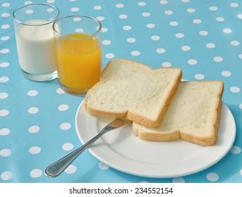 breakfast bread milk orange juice on the table
