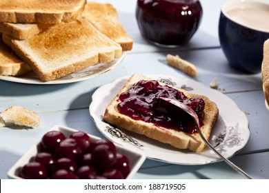 Breakfast with bread toast with cherry jam and a cup of cocoa