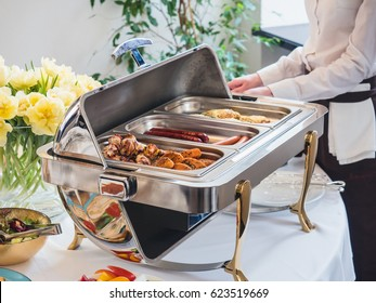 Breakfast (brunch) buffet in a fancy restaurant or hotel. Steam table with skewers and sausages, waitress in a white shirt on a background. Table decorated with flowers