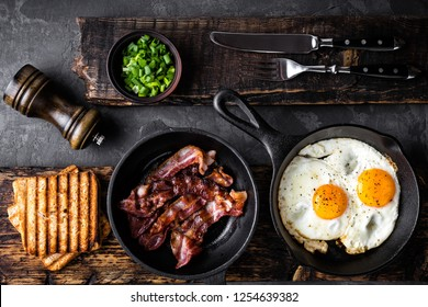 breakfast or brunch fried bacon and eggs in black skillets and crispy toasts top view