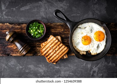 breakfast or brunch fried eggs in black skillet and crispy toasts top view with space for a text