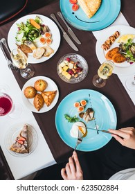 Breakfast or brunch with sparkling wine in a fancy hotel or restaurant. Female hand cutting a beautiful Poached egg, crepes with caviar on a background, mini pies and cheeses on a plate. Diagonal