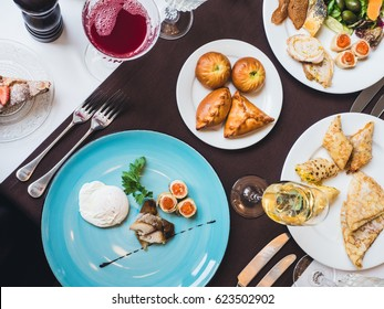 Breakfast or brunch with sparkling wine in a fancy hotel or restaurant. Poached egg with mackerel fish and crepes with caviar on a blue plate. Mini pies and variety of crepes on a background.