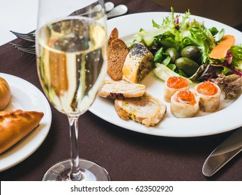 Breakfast or brunch with sparkling wine in a fancy hotel or restaurant. Crepes with caviar, greens and other food. Mini pies and variety of crepes on a background.