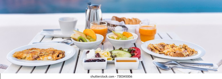 Breakfast brunch table fruits and omelettes for couple honeymoon at restaurant. Cruise vacation holiday travel destination, luxury hotel food panoramic crop.