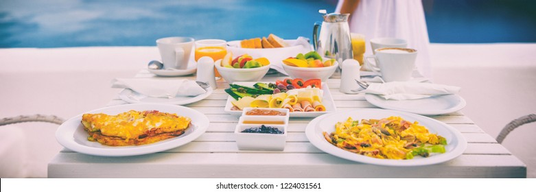 Breakfast brunch travel vacation hotel table with view of Mediterranean sea in Santorini, Greece, Europe. Luxury healthy food table for two to eat outside on cruise ship deck.