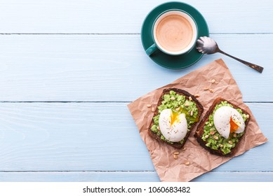 breakfast bruschetta with avocado and spinach and poached egg. with a cup of coffee