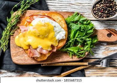 Breakfast Burger with bacon, egg Benedict, hollandaise sauce on brioche bun. Garnish with arugula salad. White background. Top view