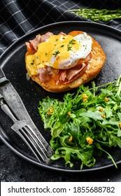Breakfast Burger with bacon, egg Benedict, hollandaise sauce on brioche bun. Black background. Top view