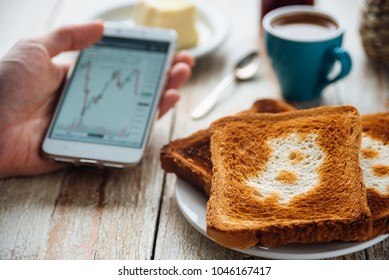 Breakfast of businessman with coffee and phone. Toast with bitcoin symbol. Bitcoin exchange rate on phone screen