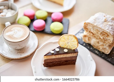Breakfast in the cafe, morning coffee. Cappuccino and lots of desserts on the table. Napoleon, chocolate cake, cheesecake and macaroons.