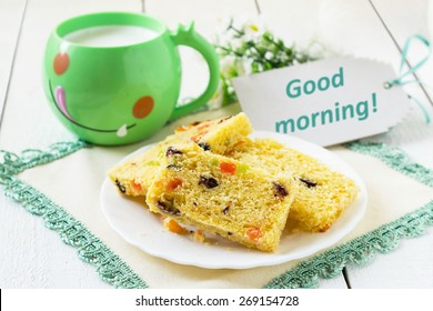 Breakfast Cake With Candied Fruit And Milk In A Green Mug On White Wooden