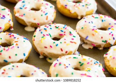 Breakfast of cake doughnuts with white icing and sprinkles
