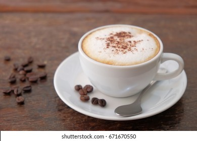 Breakfast cappuccino coffee and roasted coffee bean on vintage wooden table background