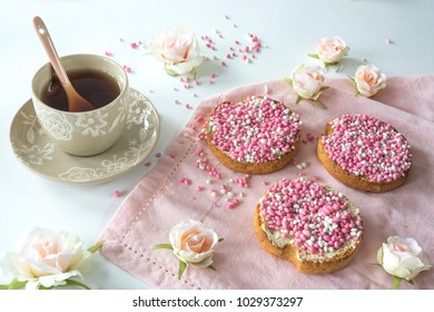 breakfast celebration birth of a daughter with roses, cup of tea and rusk with traditional Dutch food pink muisjes, aniseed