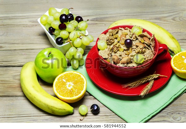 Breakfast with cereal bran flakes in red bowl placed with nuts,fresh grapes,orange, banana, green apple and cherries on wooden background. Top view