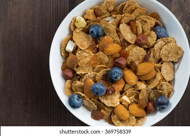 breakfast cereal flakes with blueberries and nuts on a dark wooden table, top view closeup, horizontal