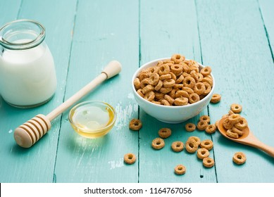 breakfast cereal with milk, honey on blue wood table