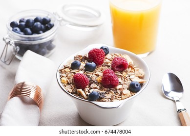 Breakfast cereal with raspberries and blueberries next to orange juice.