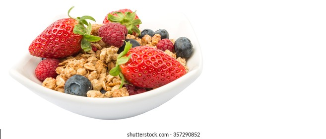 Breakfast cereal with strawberry, raspberry and blueberry in white bowl over white background