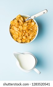 Breakfast cereals or cornflakes in bowl and milk on blue background. Top view.