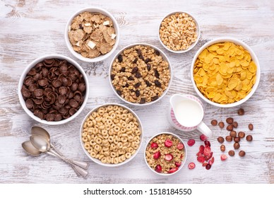 Breakfast cereals in white bowls on white wooden table, top view