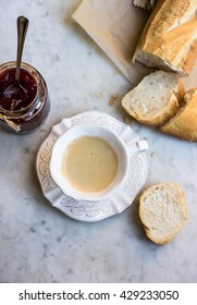 Breakfast with coffee, bread and strawberry jam on a marble table