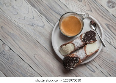 Breakfast with coffee and Cannoli - Italian pastries, a staple of Sicilian cuisine, with creamy filling usually containing ricotta.