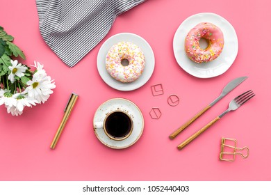 breakfast with coffee, donuts and flowers on pink background top view