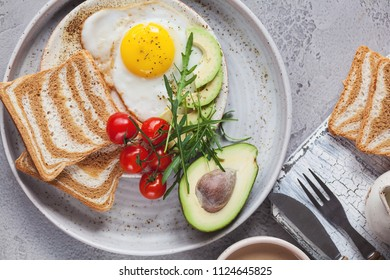 breakfast of coffee and fried egg with avocado, tomatoes and bread